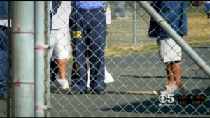 inmates stand in prison yard behind chain link fence